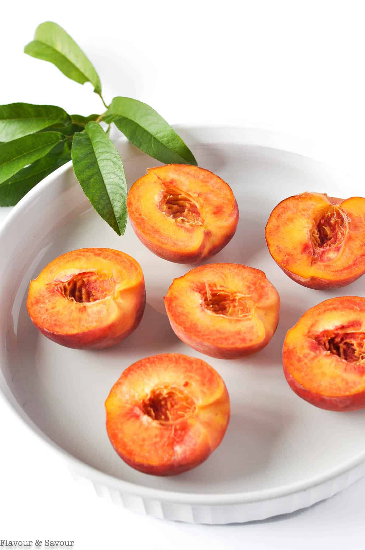 Peach halves in a white shallow dish with peach leaves