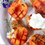 Close up view of grilled peaches topped with whipped cream