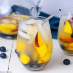 A glass of The Best Peach Sangria with fresh peaches and blueberries.