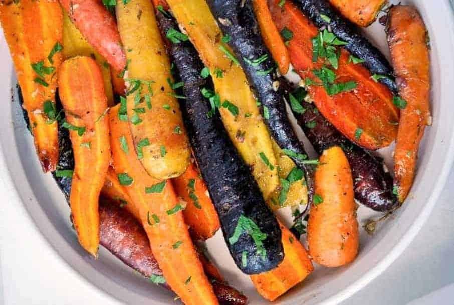 Rainbow coloured Roasted Carrots with Honey-Mustard Glaze garnished with parsley