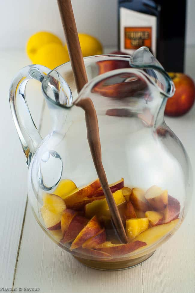 Fresh peaches in a pitcher for making Peach Sangria