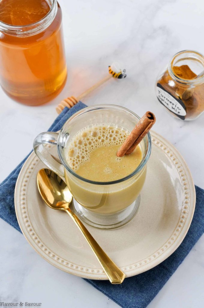 Turmeric Cinnamon Milk with a jar of honey in the background
