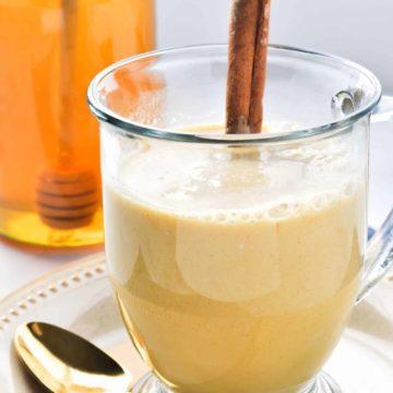 Warm Turmeric Cinnamon Milk in a clear mug with a cinnamon stick
