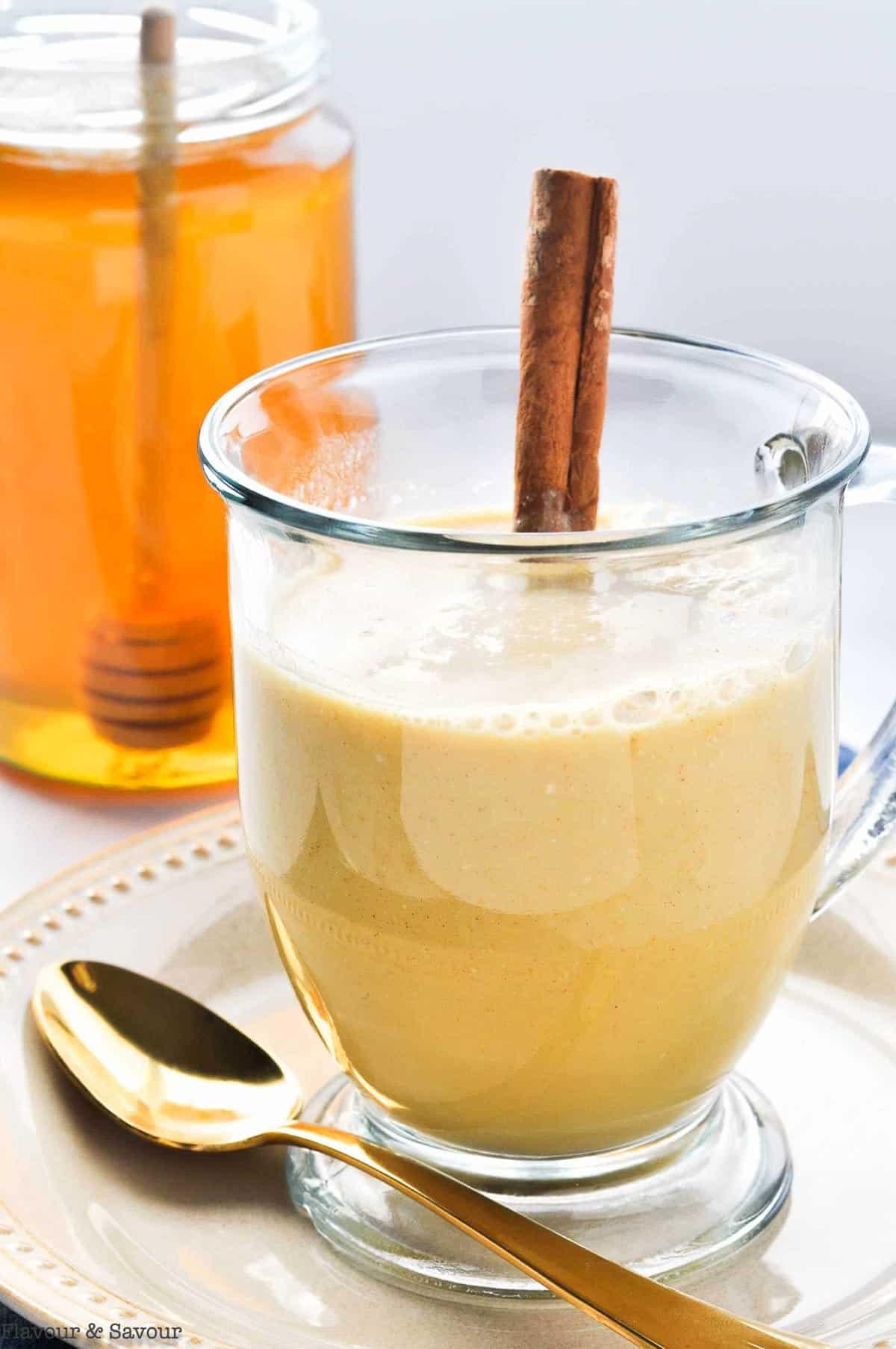 Warm Turmeric Cinnamon Milk in a glass mug with a cinnamon stick