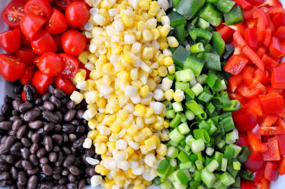 Fresh Burrito Bowl ingredients: tomatoes, black beans, corn, green onions, red peppers