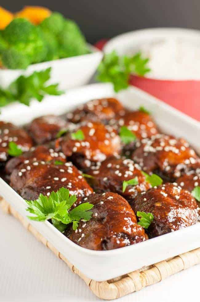 Slow Cooker Sticky Chicken thighs in a white serving dish garnished with sesame seeds