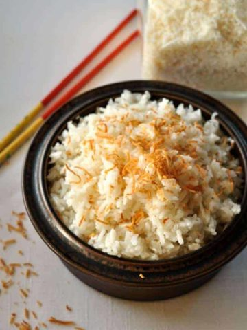 Thai Coconut Rice in a brown stoneware dish with chopsticks.