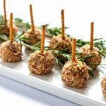 Mini Cheese Balls skewered with a pretzel stick. on a white platter.