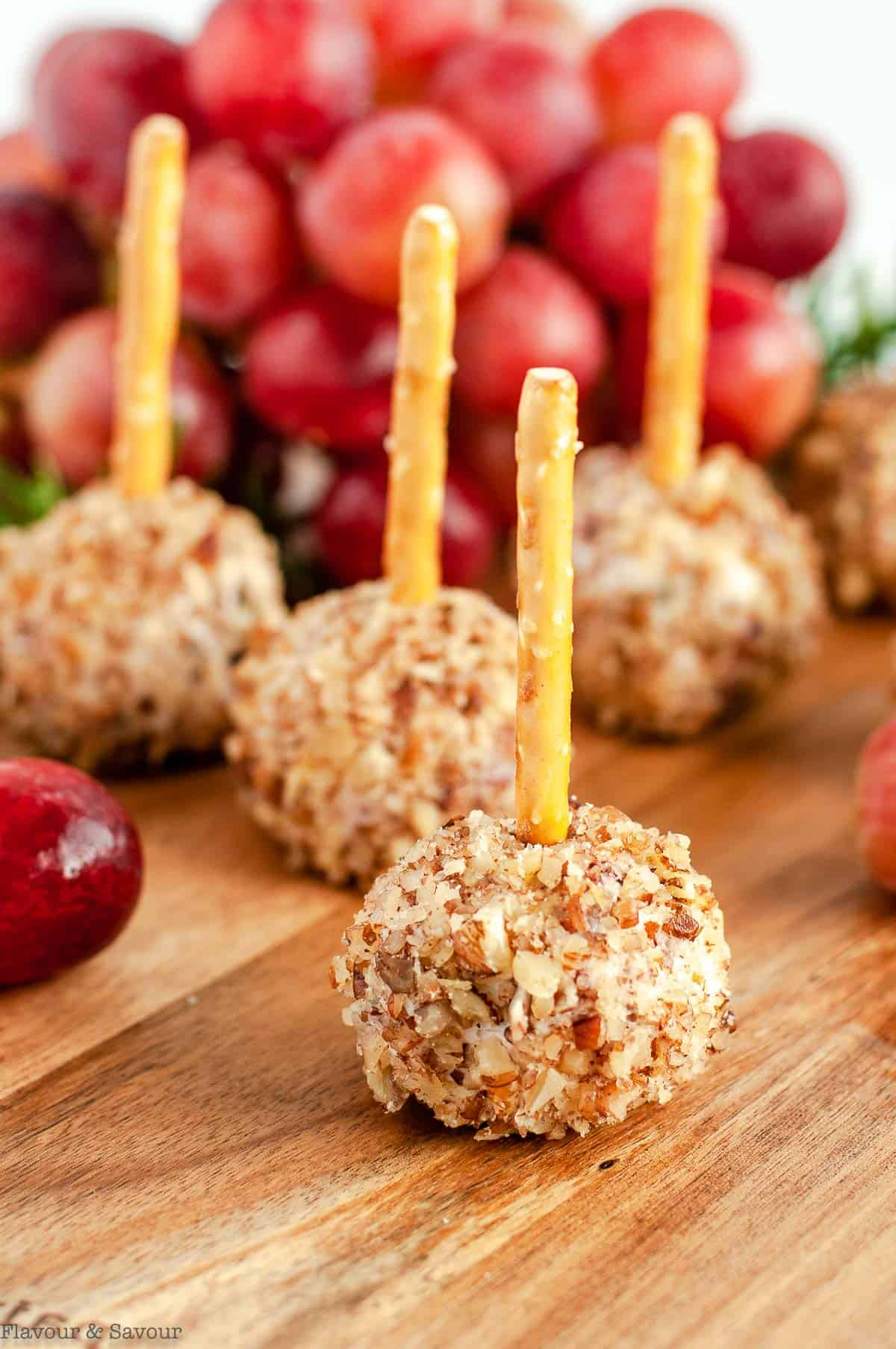 close up view of Mini Cheese balls with pretzel sticks on a board with grapes