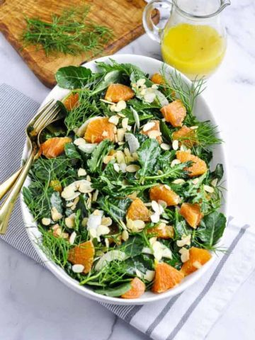 A shallow bowl of kale salad with Cara Cara oranges and toasted almonds