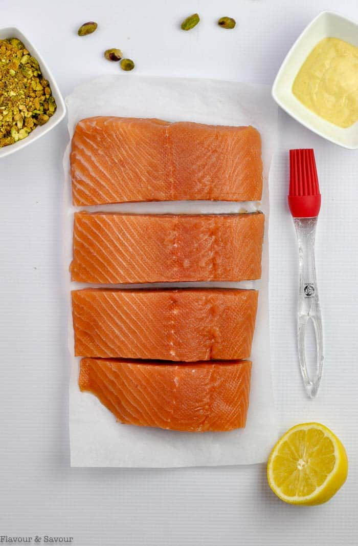 one large salmon fillet cut into 4 pieces with olive oil, a lemon, crushed pistachios and a pastry brush beside.