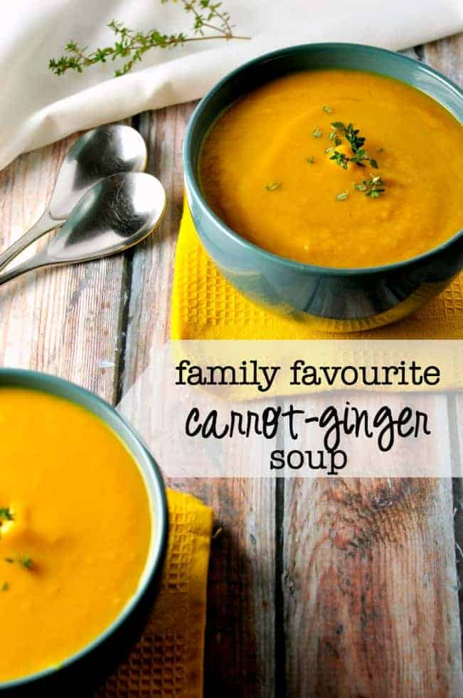 Two bowls of carrot-ginger soup garnished with fresh thyme