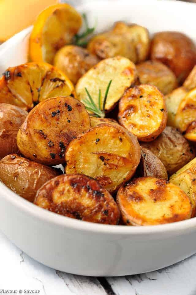 Crispy Lemon Oven Roasted Potatoes in a white bowl.