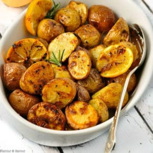 Crispy Lemon Oven Roasted Potatoes in an oval dish with a serving spoon