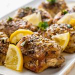 Easy Baked Lemon Chicken on a serving platter with fresh herbs and lemon