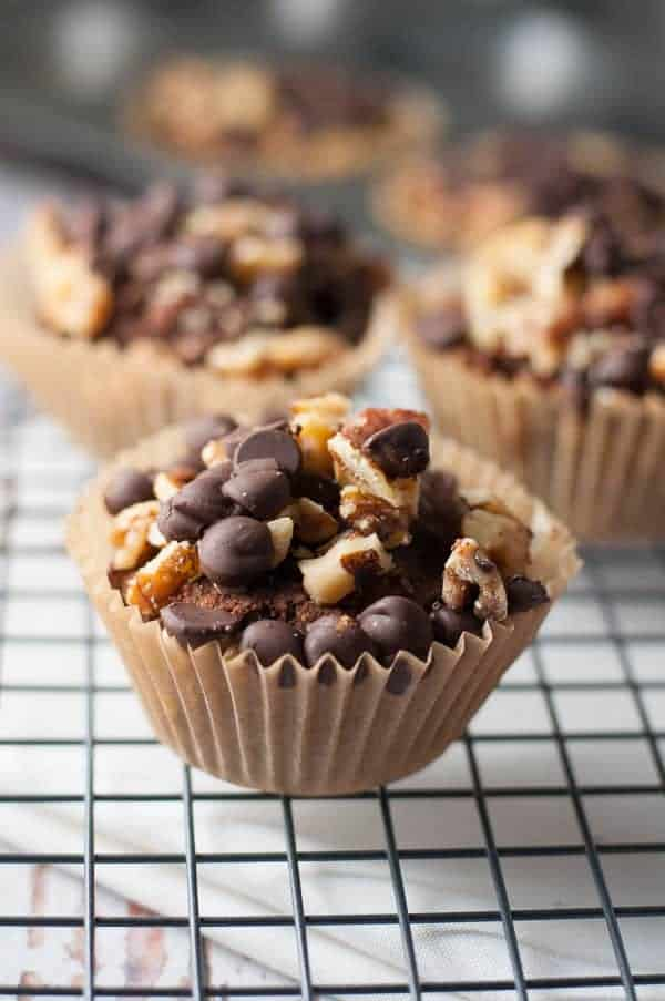 Chunky Monkey Muffins topped with walnuts and chocolate chips on a cooling rack.