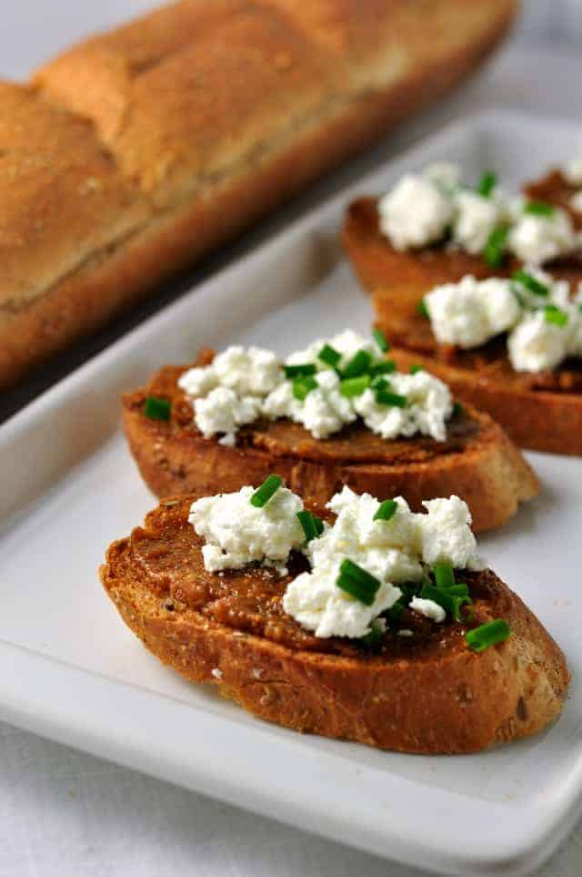 Fig and Goat Cheese Crostini garnished with chopped green onion.