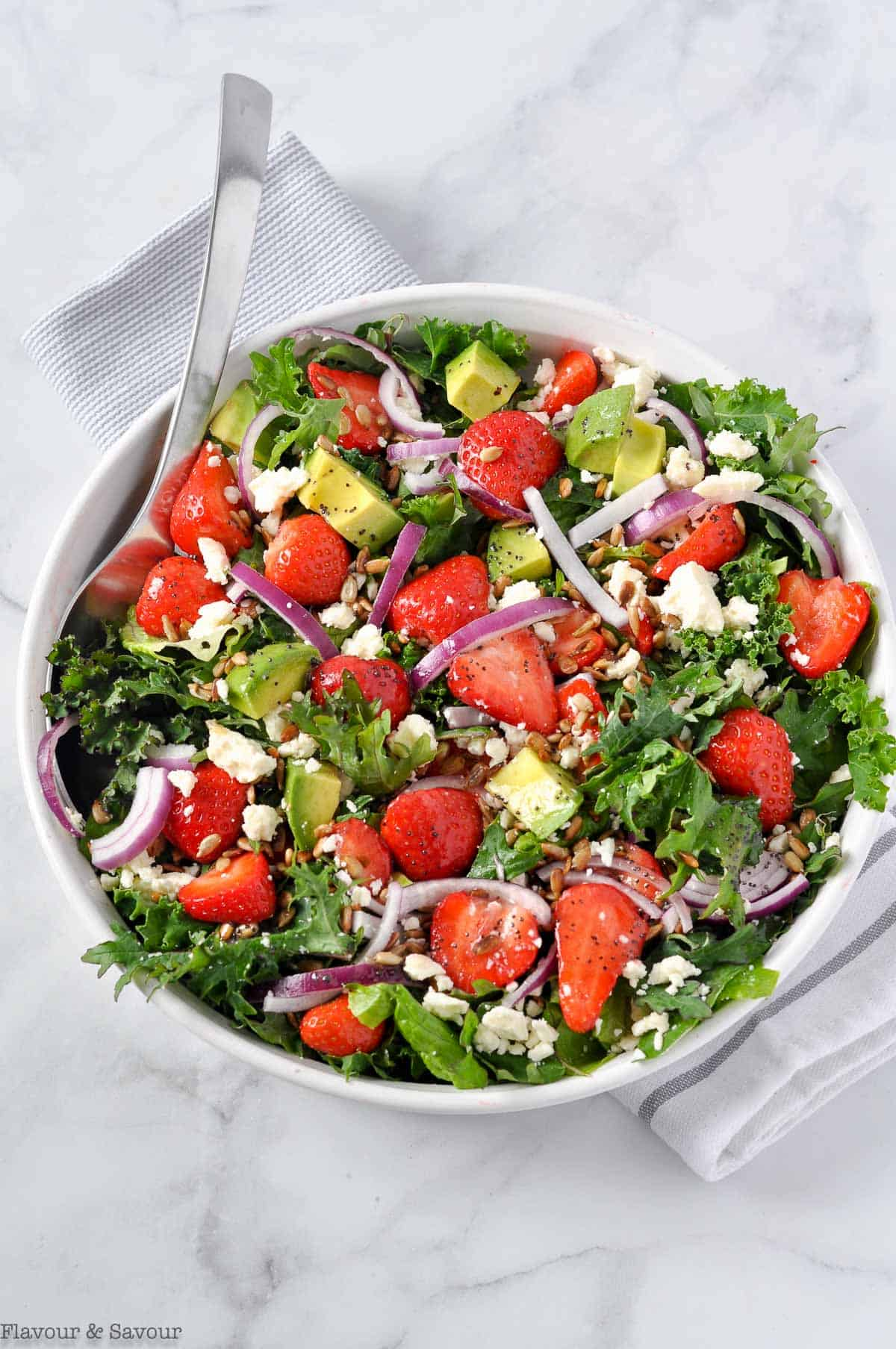 Overhead view of Strawberry Kale Salad with Poppy Seed Dressing on a marble slab