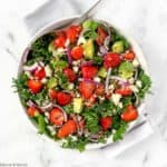 overhead view of a round white dish of Strawberry Kale Salad