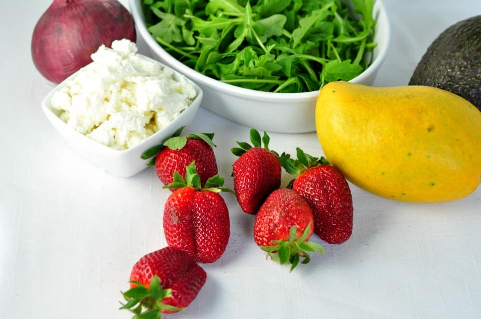 Ingredients for strawberry mango salad. Arugula, red onion, goat cheese, strawberries, mango and avocado