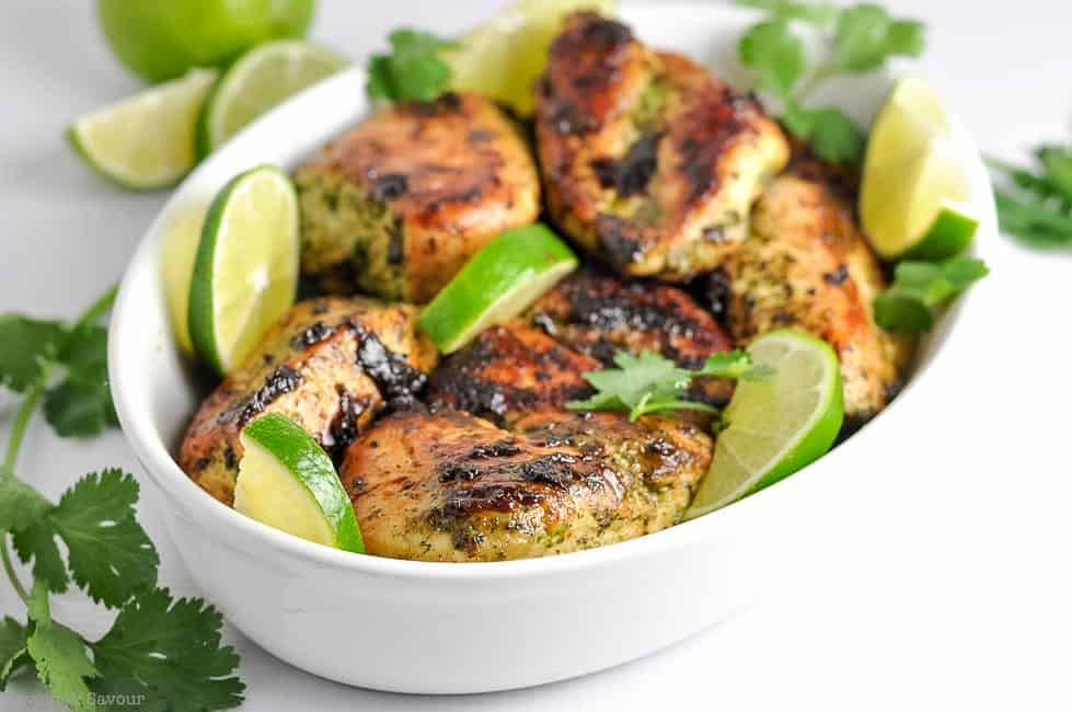 Easy Thai Baked Chicken thighs with lime slices in a serving bowl