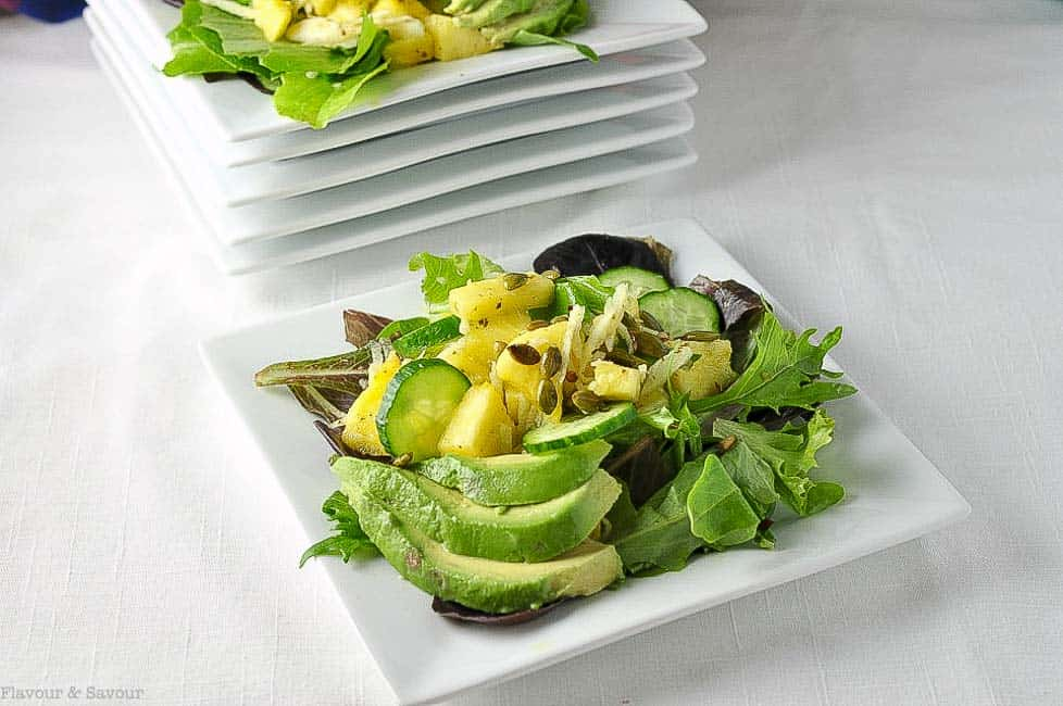 Paleo Pineapple Jicama Salad on a square plate. Mixed green topped with pineapple chunks, thinly sliced jicama, cucumber and sliced avocado.