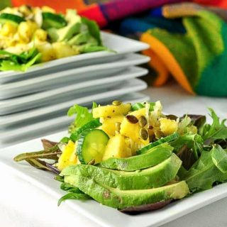 Pineapple Jicama Salad arranged on a square white plate with avocado slices