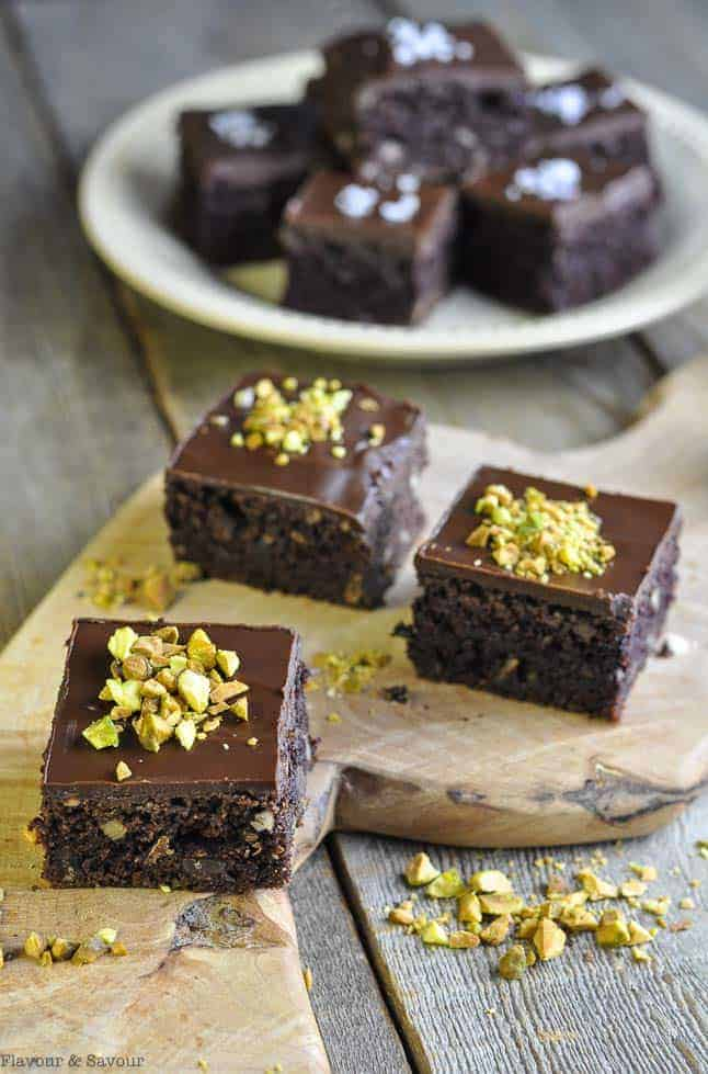 Brownies topped with ganache and salted pistachios on a wooden board