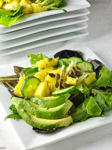 Pineapple Jicama Salad with avocado slices arranged on a white plate