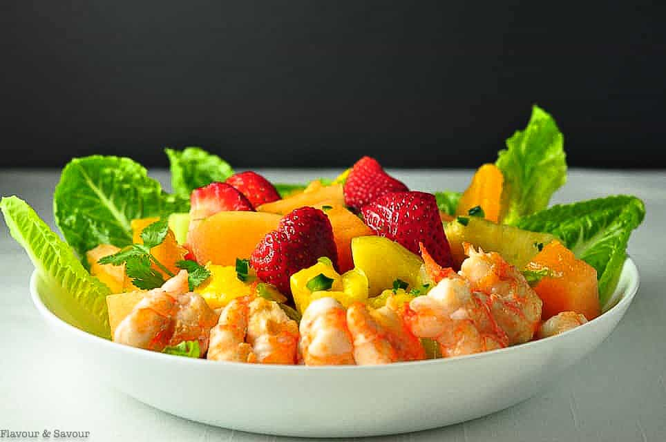 Southwestern Prawn and Fruit Salad in a white shallow bowl with strawberries, melon and mango