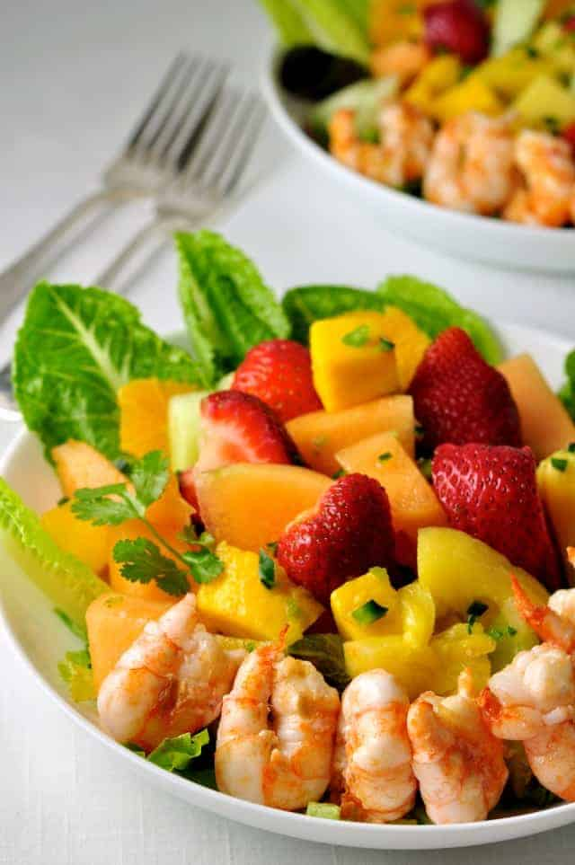 Southwestern Fruit Salad with grilled prawns in a white shallow bowl