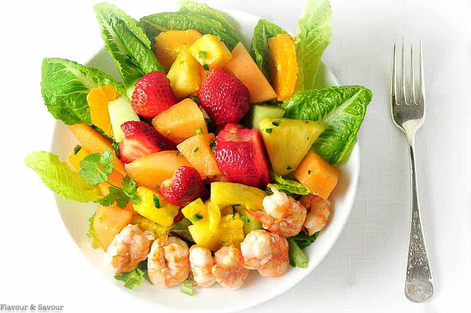 Overhead view of Shrimp Fruit Salad with strawberries and melon with a fork beside