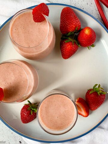 overhead view of 3 glasses of strawberry rhubarb smoothie