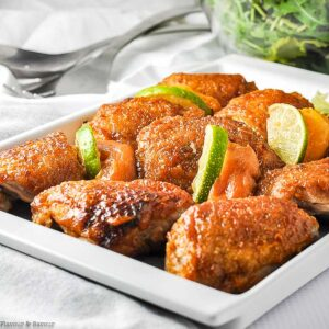 a platter of chipotle peach chicken with lime slices