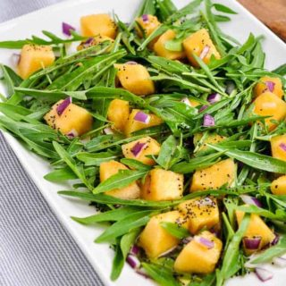 Cantaloupe Arugula Salad on a white platter