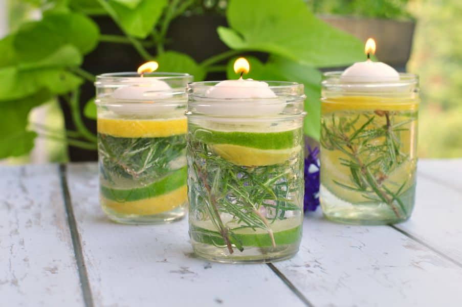 Natural Bug Repellent Luminaries using essential oils in small Mason jars with herbs and lemon and lime slices.