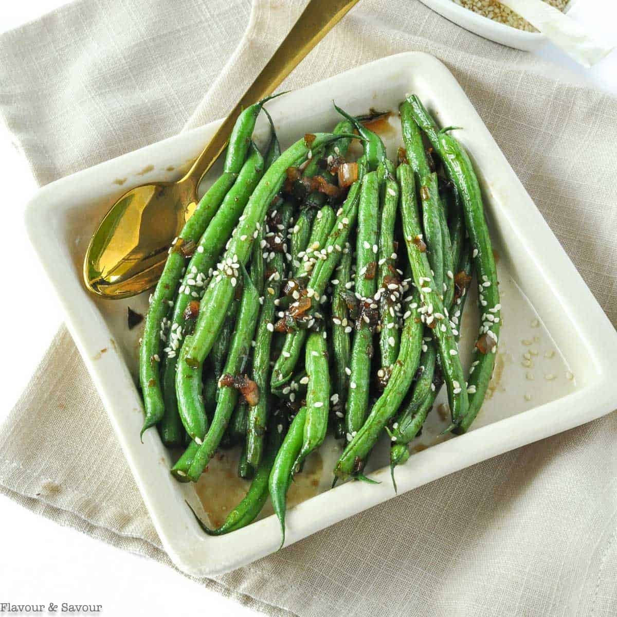 Sesame Ginger Green Beans in a square serving dish with a gold spoon