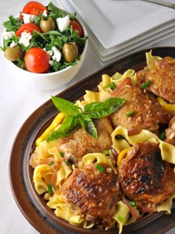 Lemon Garlic Chicken with Pasta and Herbs on a brown oval serving dish, garnished with basil.