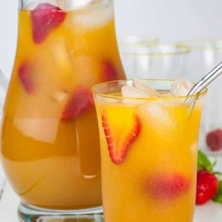 A pitcher and a glass of Peach Ginger Iced Green Tea garnished with strawberries.