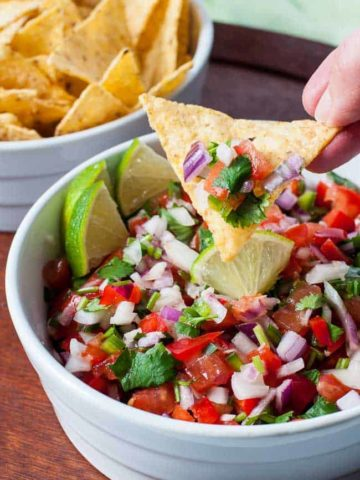 Scooping Pico de Gallo with tortilla chips