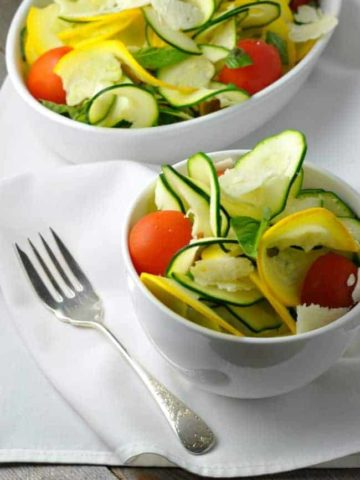 Two bowls of Zucchini Basil and Parmesan Salad with a fork.