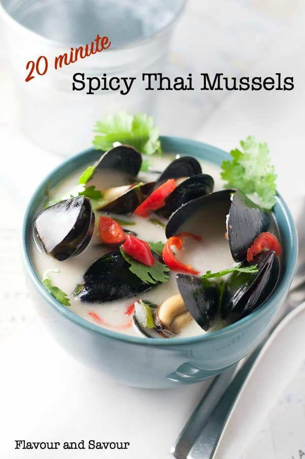 A bowl of Spicy Thai mussels garnished with cilantro and Thai red chili peppers.