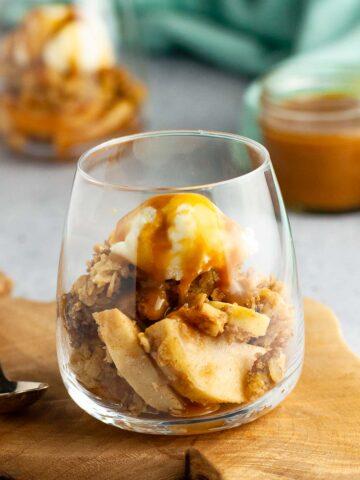 a dessert glass with apple crisp, ice cream and salted caramel bourbon sauce