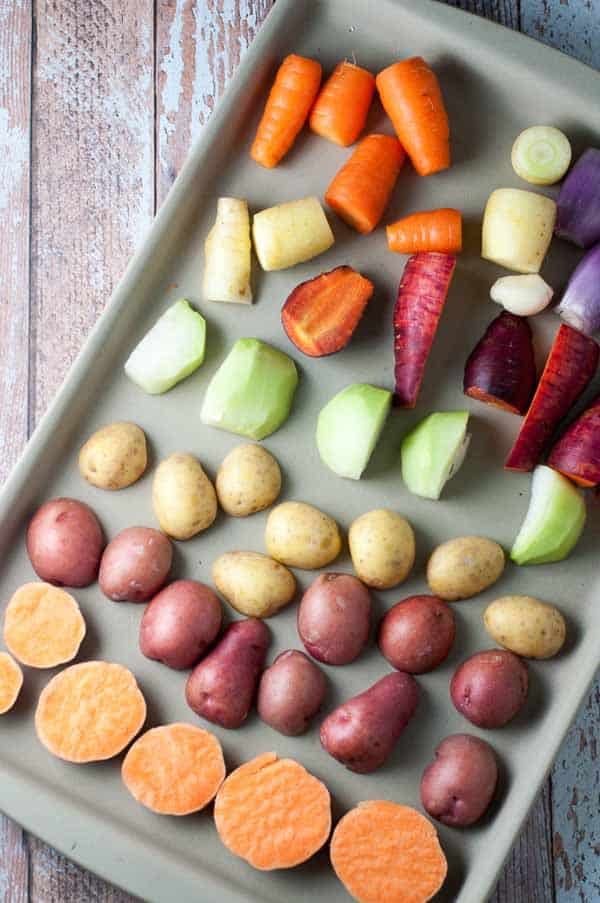 Crispy Apple Cider Roasted Root Vegetables ready for the oven on a baking tray