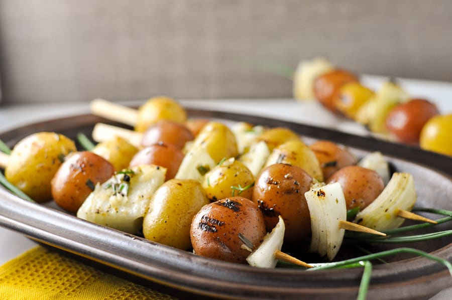 Grilled Lemon Garlic Potato Kabobs on a brown stoneward platter