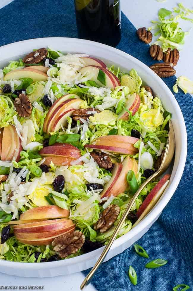Shaved Brussels Sprouts Salad with Cranberries and Pecans in a shallow white bowl with a spoon