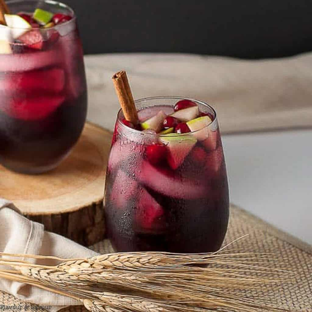 a glass of cranberry apple cider sangria with a cinnamon stick