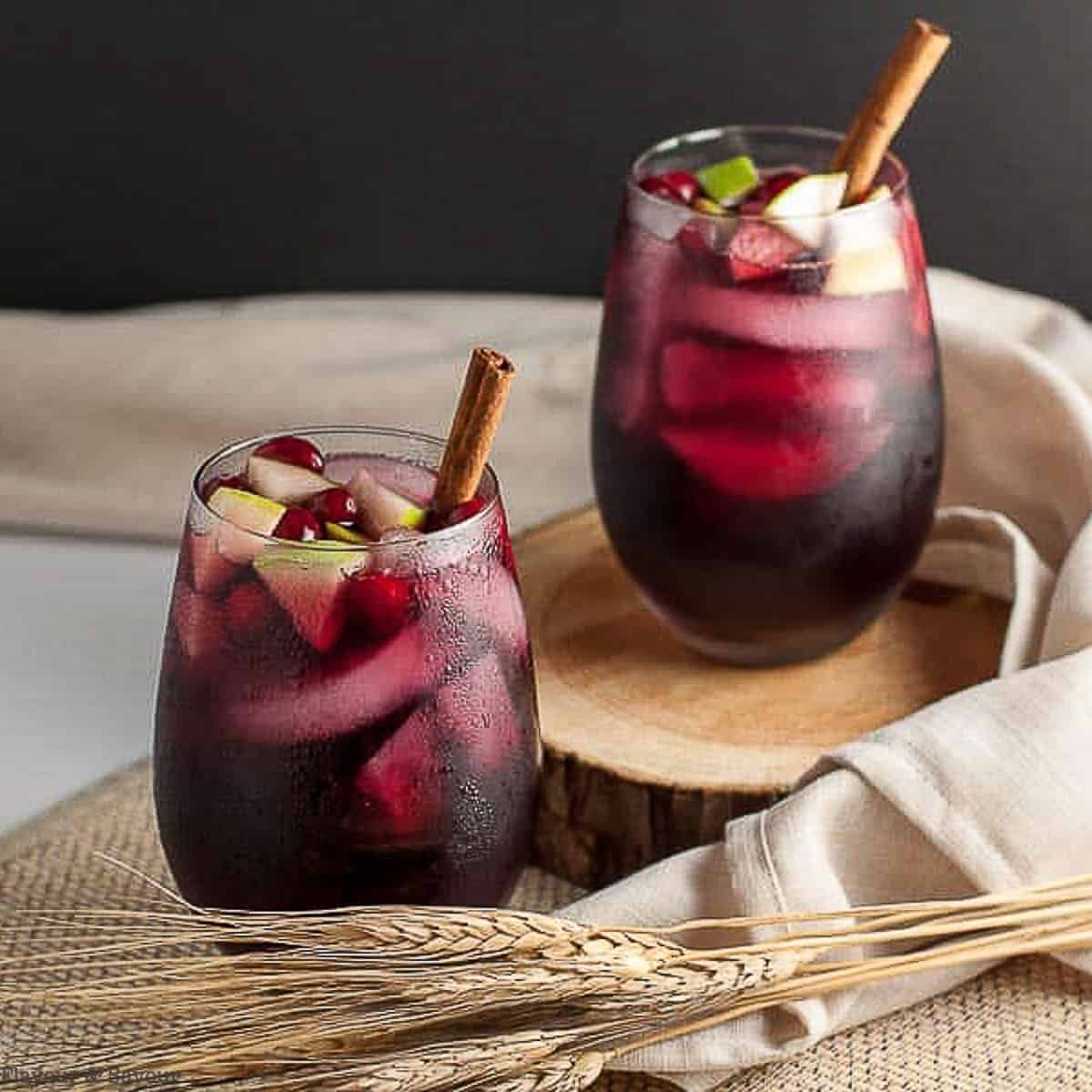 two glasses of cranberry apple cider sangria with chopped apples and cinnamon sticks