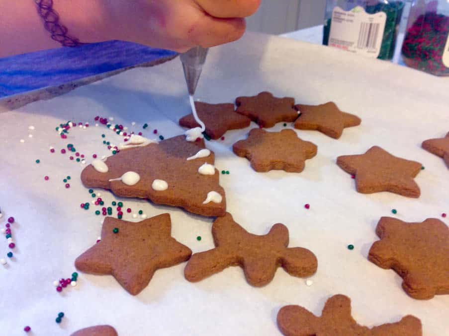 Piping icing on Gingerbread Cut-Out Cookies.