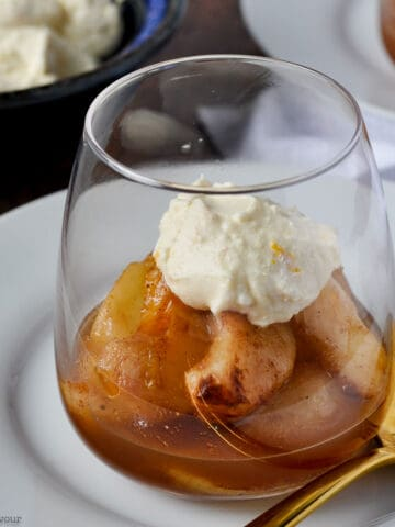 mulled cinnamon orange pears with mascarpone in a dessert glass with a spoon